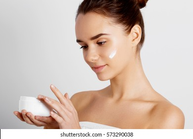 Skincare. Beauty Concept. Young pretty woman holding cosmetic cream