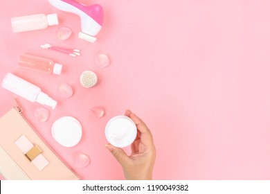 Skincare beauty treatment plant-based products with pink rose petals. Jar of body moisturizer, attar bottle toning lotion, top view homemade cosmetic ingredients.