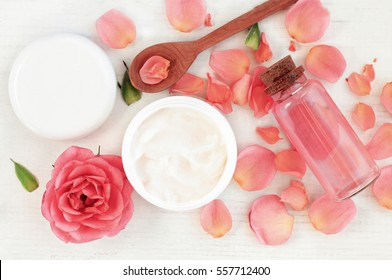 Skincare beauty treatment plant-based products with pink rose petals. Jar of body moisturizer, attar bottle toning lotion, top view homemade cosmetic ingredients