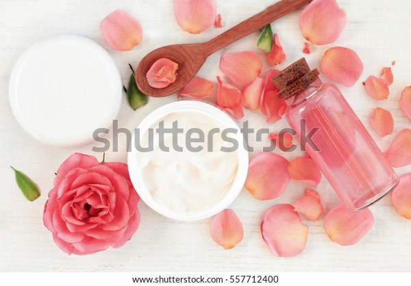 ピンクのバラの花びらを持つ、スキンケアの美容施設をベースにした製品。ボディ用保湿剤の瓶、アタールボトル用化粧水、トップビュー手作りの化粧品成分