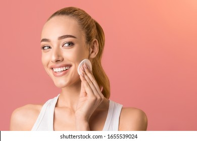 Skincare And Beauty. Young Woman Using Cotton Pad Removing Makeup And Cleansing Face Skin On Pink Studio Background. Free Space