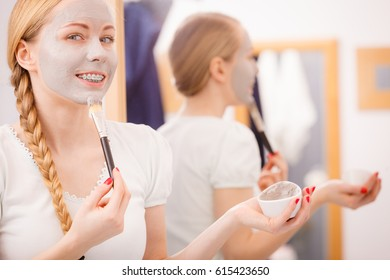Skincare. Blonde woman in bathroom applying with brush gray clay mud mask to her face. Young lady taking care of skin. Spa beauty wellness.