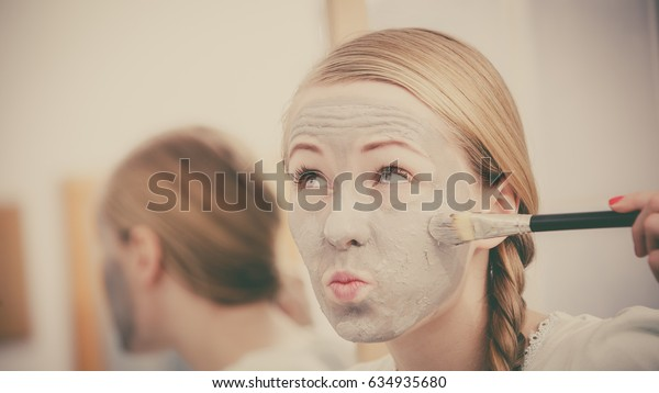 Skincare. Blonde woman in bathroom with gray clay mud mask on her face. Young lady taking care of skin. Spa beauty wellness. Toned image