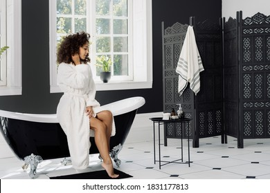 Skincare and bodycare concept. Full length view of good looking african american woman spending morning in bathroom, sitting on bath, wearing in bathrobe