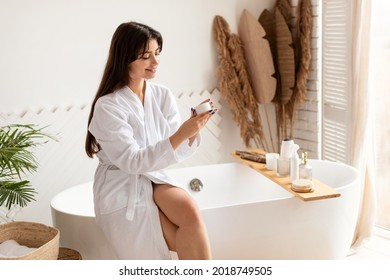 Skincare Concept. Cheerful Brunette Woman Holding Cream Moisturizer Caring For Skin Sitting In Modern Bathroom At Home. Female Beauty Rituals, Skin Care Cosmetic Products Concept