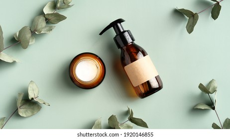 Skincare cosmetics products and eucalyptus leaves on green background top view. Flat lay jar of moisturizer cream and natural herbal shower gel in amber glass dispenser bottle. SPA treatment concept.