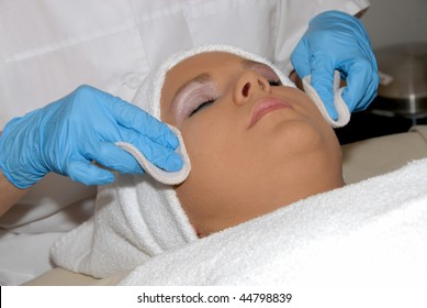 Skincare facial treatment at day spa being preformed on face of woman wrapped in a towel.