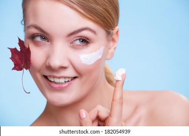 Skincare habits. Face of young woman with leaf as symbol of red capillary skin on blue. Girl taking care of her dry complexion applying moisturizing cream. Beauty treatment.