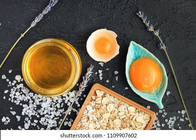 Skincare homemade natural mask made from honey and egg yolk, rolled oats, sea salt, lavender. Cosmetic ingredients top view black spa background.