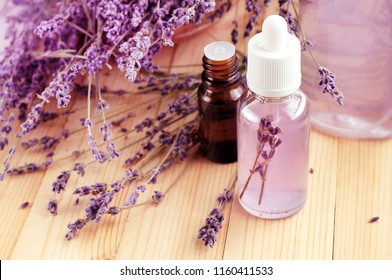 Skincare Lavender refreshing facial toner in bottle, essential oils, pink violet blossom, wooden table. Botanical extract for beauty treatment.