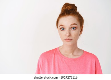 Skincare and makeup concept. Close-up of clueless young redhead woman acting confused, staring with blue eyes at camera and shrugging, standing over white background.