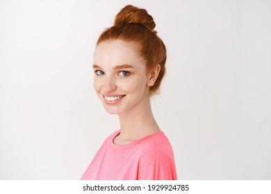 Hautpflege und Make-up Konzept. Nahaufnahme einer hübschen Rotkopffrau mit unordentlichem Bun, blauen Augen und Sommersprossen, Lächeln mit weißen Zähnen und Anblick auf Kamera, weißer Hintergrund