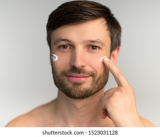 Skincare. Middle Aged Man Applying Anti-Aging Cream On Face Skin Over White Background. Studio Shot, Isolated