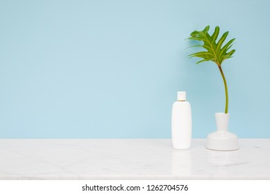 Skincare moisturizer bottle put on white marble desk table with blue sky wall background.