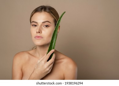 Skincare, moisturizing. Beauty Woman with perfect skin holding fresh leaf of Aloe Vera. Woman with natural makeup and healthy skin portrait