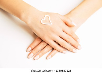 Skincare moisturizing cream in shape of heart on a female young hand, concept of beauty.