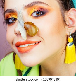 Skincare repairing. Healing mucus. Having fun with adorable snail. Cosmetics and snail mucus. Cosmetology beauty procedure. Girl fashionable makeup face and cute snail. Skin care. Massage with snail.