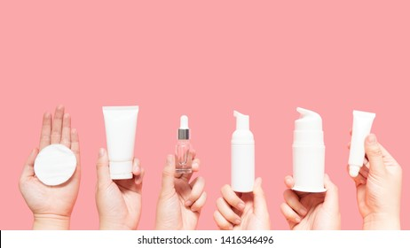 Skincare routine step for healthy skin - Woman hands holding facial cotton pad, foam, essential oil, serum, lotion and eye cream packaging on pink background. Beauty and cosmetic concept. Copy space.