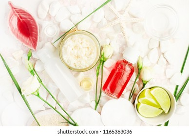 Skincare scrub with Coconut flakes in glass jar, red holistic facial lotion bottle, fresh lime and flowers viewed above on white spa stones.