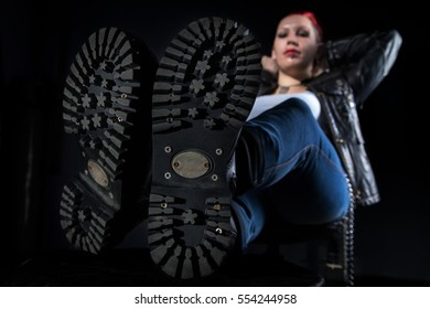 Skinhead boots and sitting woman on black background
