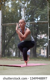 skinhead tattooed woman in yoga eagle pose, Garudasana, outdoor, summer day