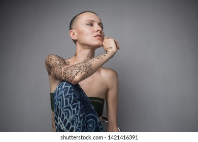 Skinhead woman portrait with mehendi on an arm and jeans