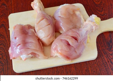 Skinless chicken thighs on a wooden cutting board. Step by step cooking