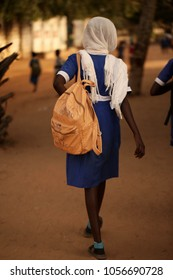 "skinny african school outdoors girl seen from the back, with blue and white school uniform and beige backpack with sign: ""gambia has decided"" in Gambia, Africa"