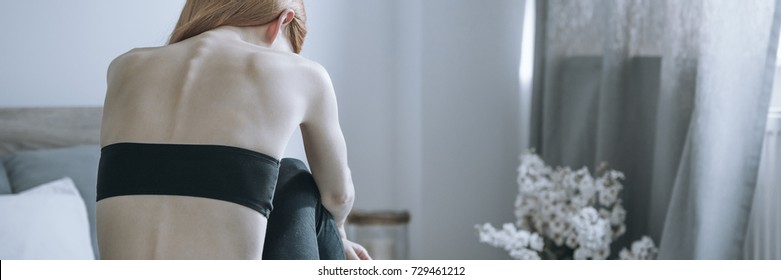 Skinny back of bulimic woman sitting depressed and alone in eating disorder treatment center