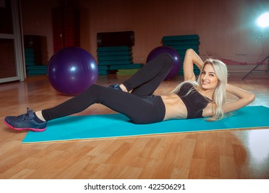 skinny blonde girl is doing exercises in a fitness room and smiling