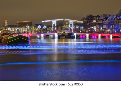 Skinny bridge in Amsterdam with light trails of passing illuminated canal bus.