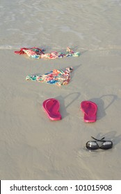 Skinny dipping concept shot showing a bikini on the beach