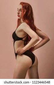 Skinny girl with red long hair is posing in the black knitted swimsuit in the studio