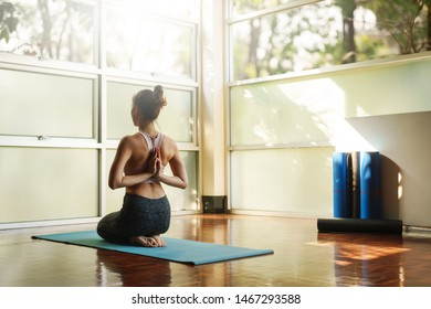 Skinny good looking asian woman practicing yoga alone in studio room