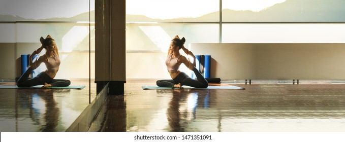 Skinny good looking asian woman practicing yoga alone in studio room with reflection in mirror