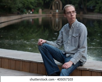 Skinny guy nerdy in the park against the backdrop of the lake