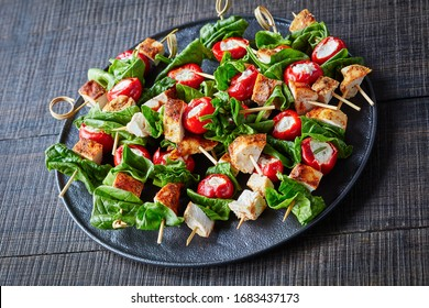 Skinny healthy appetizer: roasted with paprika chicken, peppers stuffed with cream cheese,  and spinach on skewers on a black plate on a dark wooden table, horizontal view, close-up, top view