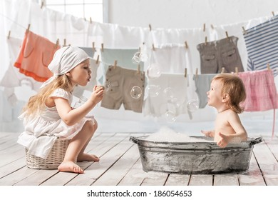 Skinny little girl in a basin for washing clothes in the laundry room