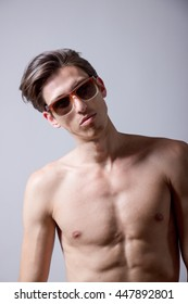Skinny model showing abs, wearing eyeglasses. Upper body shot. Clean background.