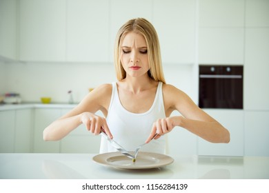 Skinny obsessed lady poor lifestyle nutrition concept. Close up photo portrait of stressed grimacing crying wearing white tshirt girl trying to chop mini tiny pea on empty plate sitting at the table