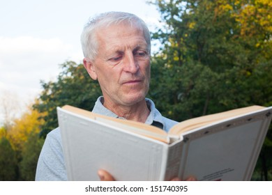 skinny  old man reading book in the park outdoor