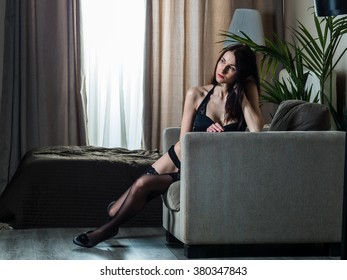Skinny Russian brunette girl in black stockings and black shoes posing on a chair in the bedroom
