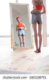 Skinny and slim. Extremely skinny and slim anorexic woman looking into mirror while measuring waistline