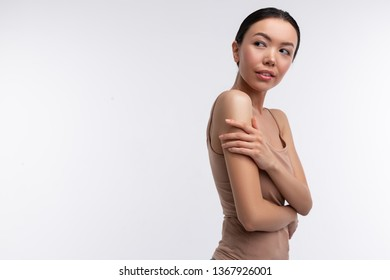 Skinny woman. Skinny dark-eyed woman wearing beige camisole standing near background touching her shoulder