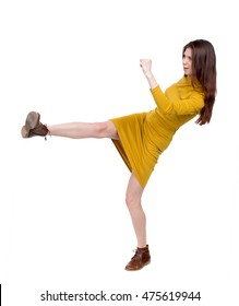 skinny woman funny fights waving his arms and legs. Isolated over white background. Girl dress in mustard foot kick.