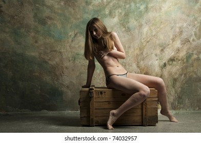 Skinny woman sitting on a wooden chest
