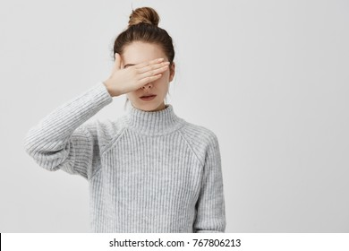 Skinny woman wearing grey outfit closing her eyes with hand. Confident female trying to hide her face from other people prefer not to see. Decision, human concept