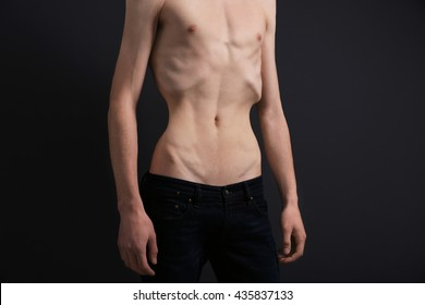 Skinny young man with anorexia on dark background
