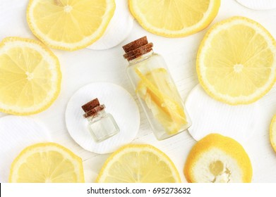 Skin-whitening homemade lemon facial care. Bright yellow citrus slices, bottles with aromatic lotion and zest, top view