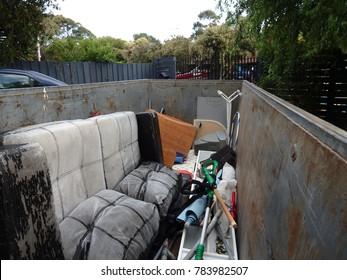 skip bin full of waste in a front yard